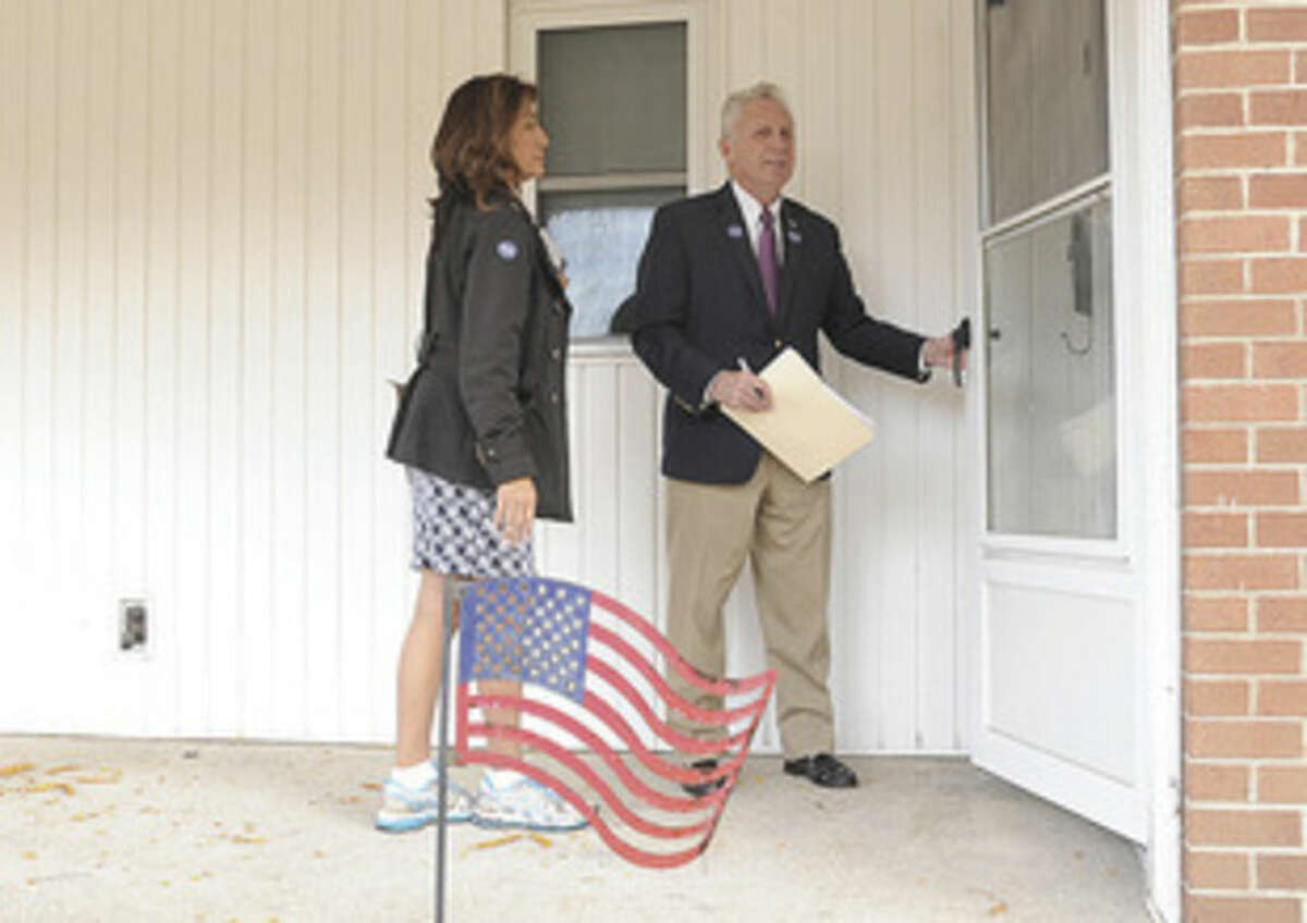 Hour photos/Matthew Vinci Norwalk Mayor Harry Rilling and his wife, Lucia, knock on doors Monday afternoon to speak to residents at the Senior Apartments in Norwalk before Tuesday's election.