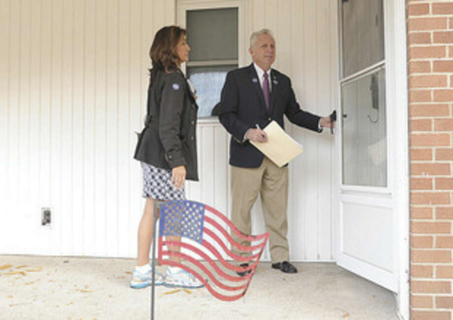 Hour photos/Matthew VinciNorwalk Mayor Harry Rilling and his wife, Lucia, knock on doors Monday afternoon to speak to residents at the Senior Apartments in Norwalk before Tuesday's election.