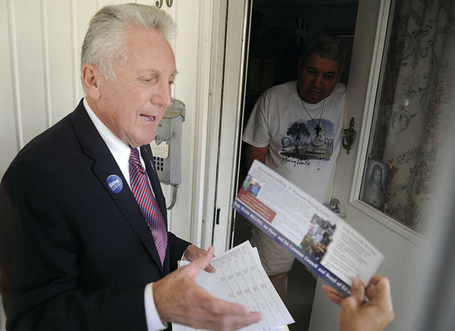 Above left, Norwalk Mayor Harry Rilling knocks on doors, greeting residents at the Senior Apartments on Union Avenue on Monday afternoon. Rilling is running for re-election as mayor in today's elections.Above right, Norwalk mayoral candidate Kelly Straniti, along with David McCarthy and Enrique Santiago, greet and hand out information to Devon Skehan Monday night at the Rowayton train station as they met commuters on the evening rush.