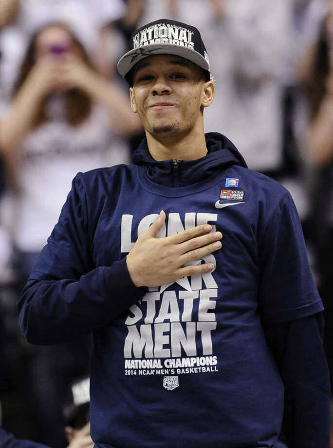 Connecticut's Shabazz Napier places his hand over his heart as he is cheered on by fans at a pep rally celebrating the program's fourth national championship, Tuesday, April 8, 2014, in Storrs, Conn. (AP Photo/Jessica Hill)