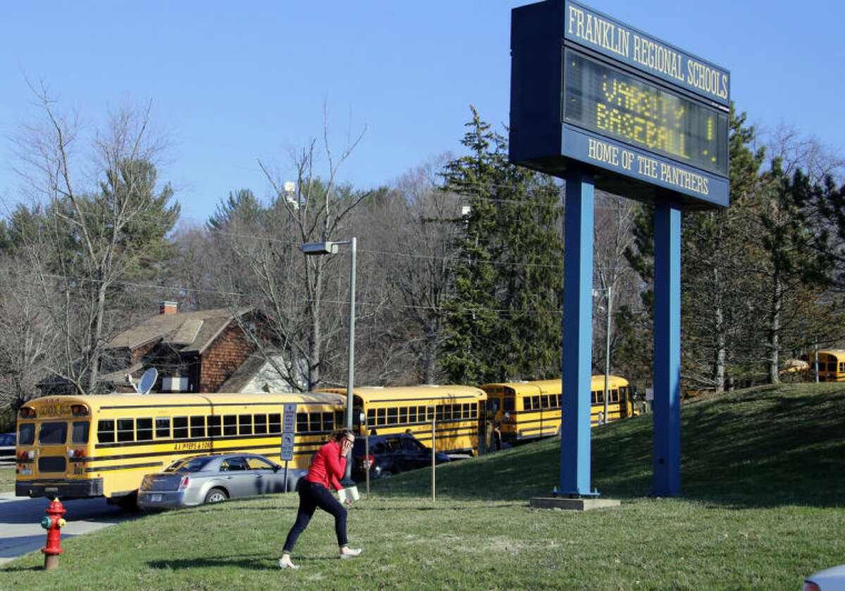 A woman walks onto the campus of the Franklin Regional School District where several people were stabbed at Franklin Regional High School on Wednesday, April 9, 2014, in Murrysville, Pa., near Pittsburgh. The suspect, a male student, was taken into custody and being questioned. (AP Photo/Keith Srakocic)