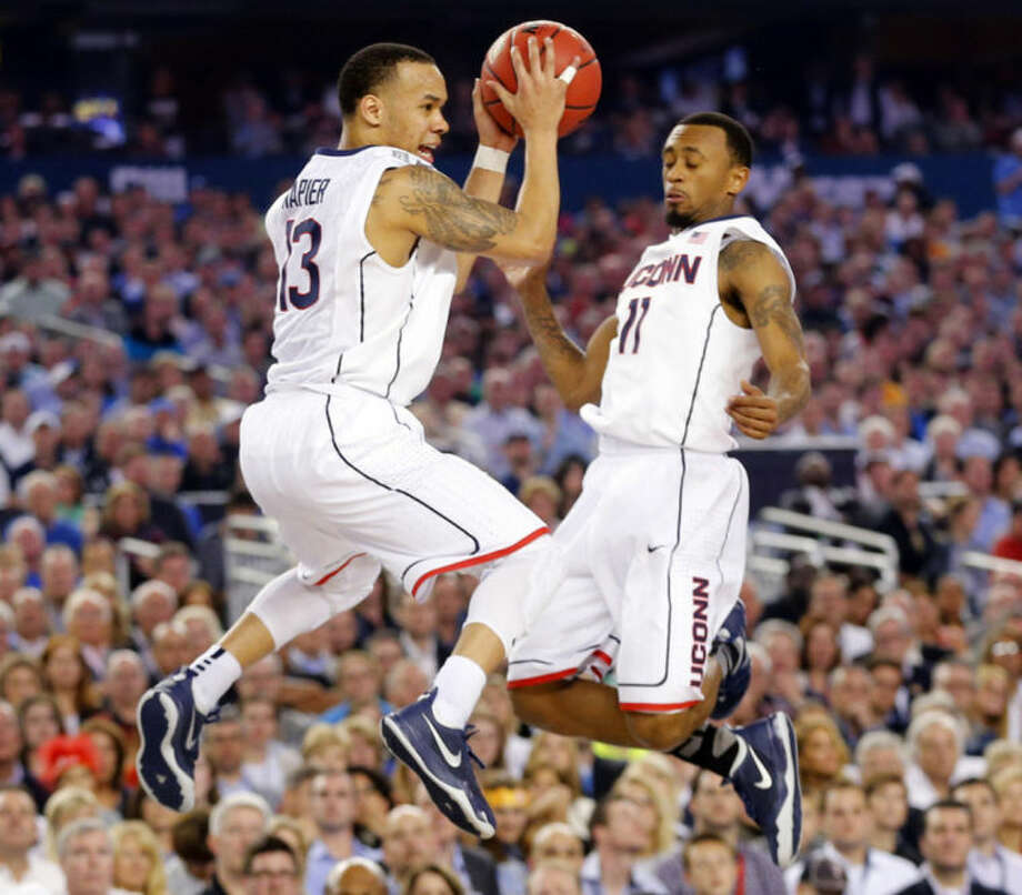 Connecticut guards Shabazz Napier (13) and Ryan Boatright (11) nearly collide during the second half of the NCAA National Basketball Championship at AT&T Stadium in Arlington, Texas on Monday, April 7, 2014. (AP Photo/The Dallas Morning News, Tom Fox)