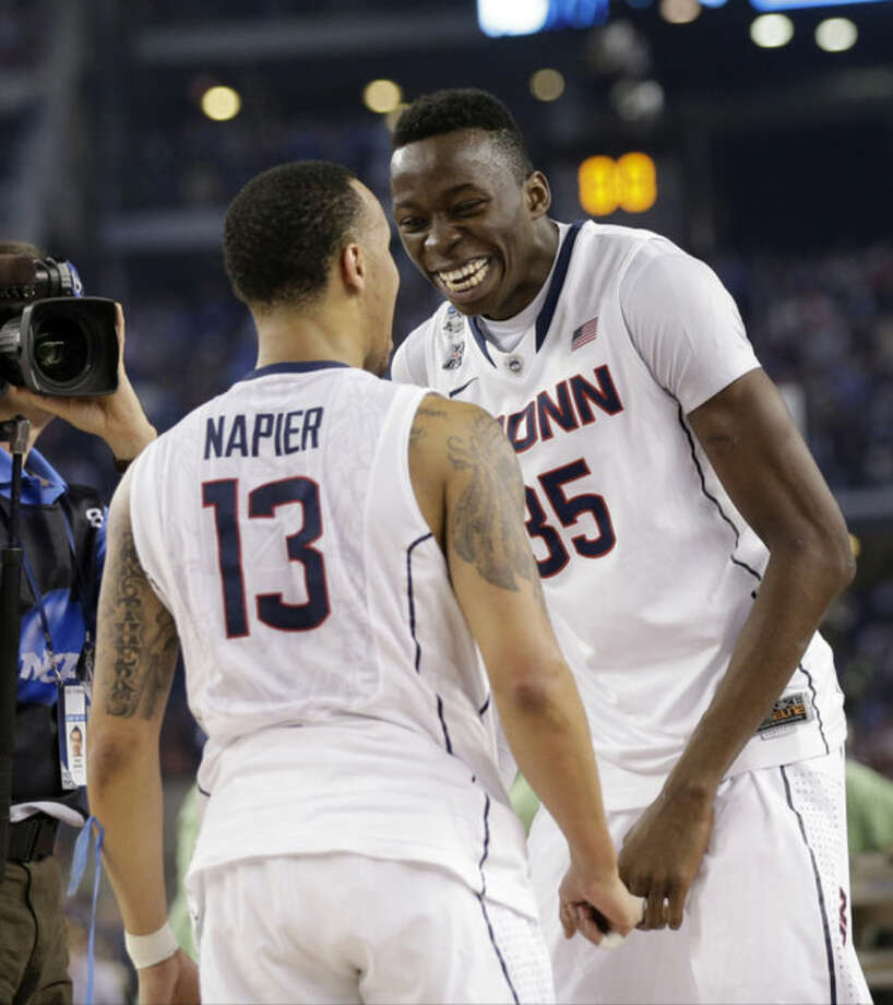 Connecticut guard Shabazz Napier (13) and center Amida Brimah (35) celebrate after beating Kentucky 60-54 at the NCAA Final Four tournament college basketball championship game Monday, April 7, 2014, in Arlington, Texas. (AP Photo/Eric Gay)