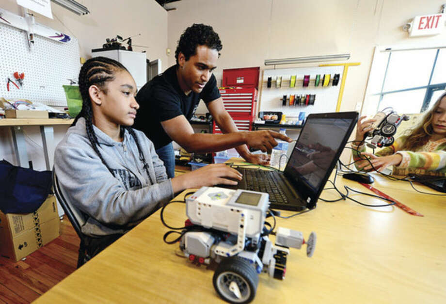 Hour photo / Erik TrautmannAngel Coleman, 14, learns to program a robot to navigate an obstacle course and complete various challenges using EV3 programming software with the help of Vladimir Mariano during the Intro to Robotics with Lego Mindstorms at the Fairfield County Makers' Guild in Norwalk Saturday.