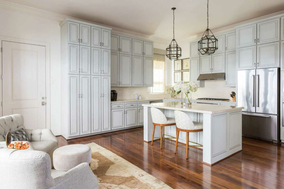 Dark kitchen cabinets were painted pale gray and then treated with antiquing finishes and silver trim.