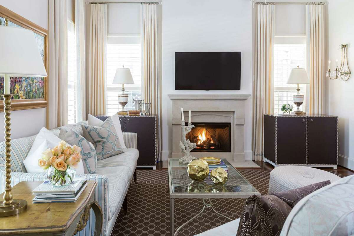A soft blue and ivory sofa coexists with dark brown cabinets and a dark rug in the living room.