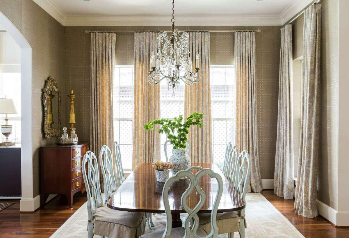 Julie Dodson aimed for casual elegance in The Woodlands home of Kristy and Brad Defenbaugh. Here, masculine wallpaper with a rivet-like finish offsets the feminine draperies, chandelier and curvy chairs. Read more.