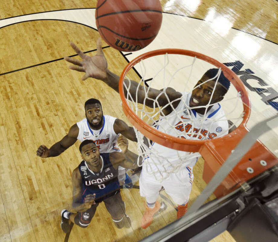 CORRECTS LOCATION TO ARLINGTON, INSTEAD OF DALLAS - Florida forward Casey Prather shoots as Connecticut forward Phillip Nolan (0) and Florida's Patric Young (4) look on during the first half of an NCAA Final Four tournament college basketball semifinal Saturday, April 5, 2014, in Arlington, Texas. (AP Photo/Chris Steppig, Pool)