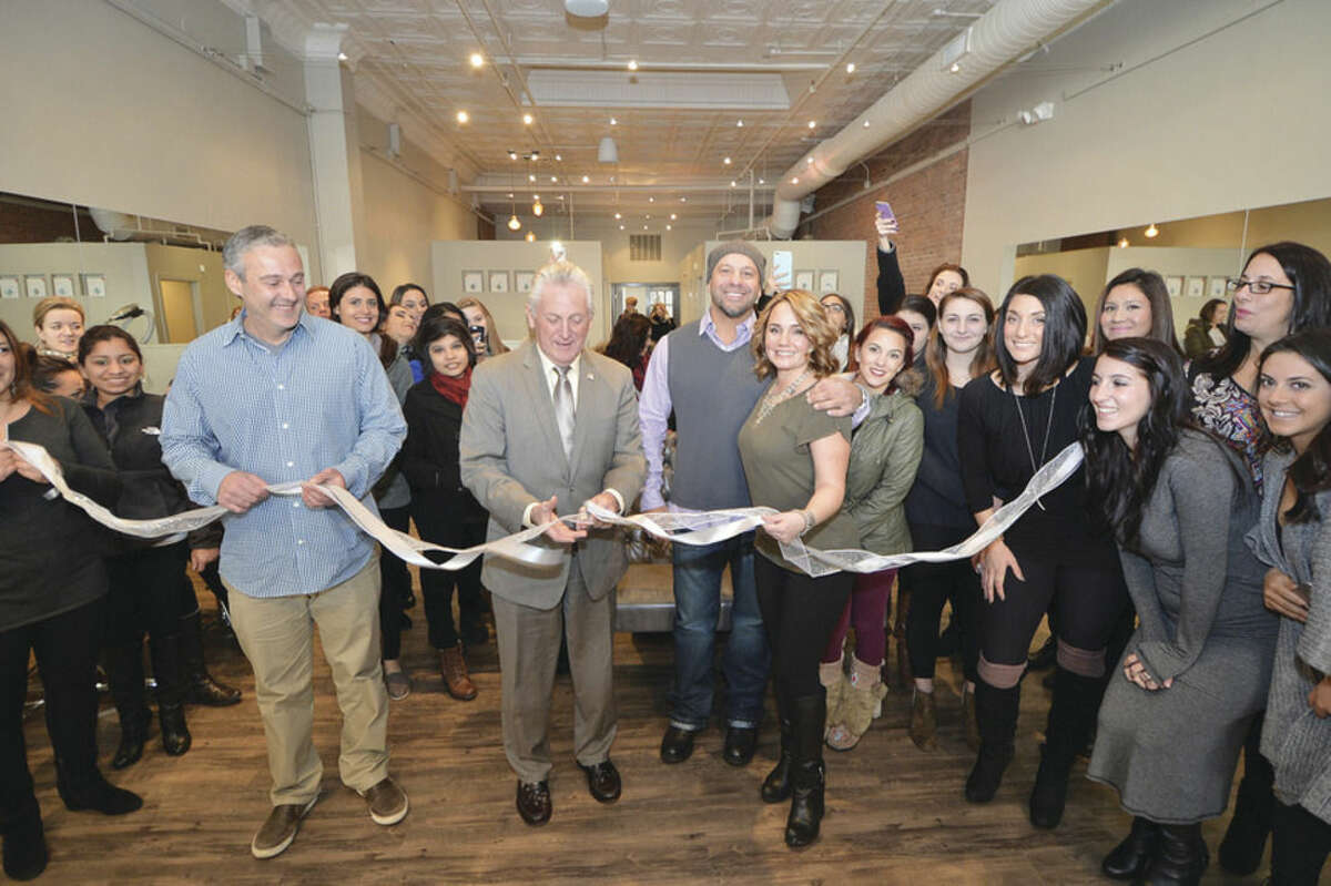 Hour Photo/Alex von Kleydorff Norwalk Mayor Harry Rilling cuts the ribbon at Etre a new salon on Washington St. with John Kydes and the owners Thea and George Tsiranides and surrounded by students from her SoNo Academy.
