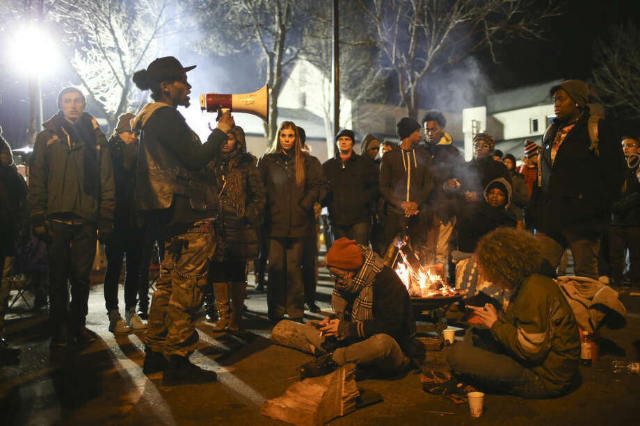 A demonstrator speaks about his encounter with attackers who were shooting at five protesters near the Minneapolis Police 4th Precinct earlier in the night, as protesters gather in front of the precinct in Minneapolis on Tuesday, Nov. 24, 2015. Minneapolis police were searching Tuesday for three white males suspected of shooting at five Black Lives Matter demonstrators, while the family of a black man who was fatally shot by a city police officer called for the dayslong protests outside of the police precinct to end. (Jeff Wheeler/Star Tribune via AP)