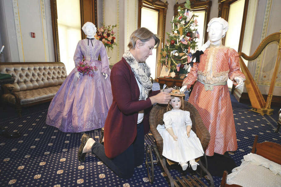 Hour Photo/Alex von KleydorffKathie Bennewitz works on setting a doll from the late 19th century in a toy stroller in one of the Vignette's for the new exhibit, Holiday Grandeur: The Mansion's toys and trains story at Lockwood Mathews Mansion Museum