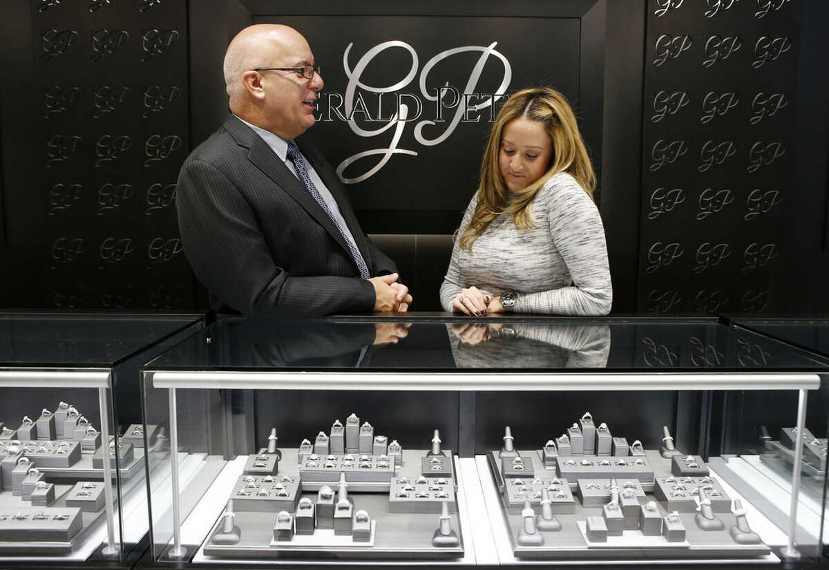 In this Wednesday, Nov. 18, 2015, photo, business owner Jerry Amerosi, left, chats with employee Alana Fusco behind the counter at Gerald Peters, one of three stores he owns in the Staten Island Mall, in the Staten Island borough of New York. Amerosi's three stores in the mall will open at 6 p.m., on Thanksgiving and stay open until midnight. He'll have eight employees working, and if this Thanksgiving is anything like last year's, they'll have their hands full.