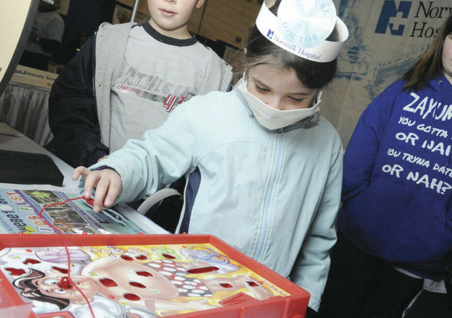 "Summer Boibeaux, 6, plays the game ""Operation"" Sunday at Kids Fest held in the Wilton High School Field House."