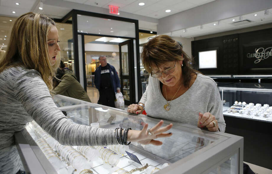 In this Wednesday, Nov. 18, 2015, photo, Alana Fusco, left, an employee at Gerald Peters, a jewelry store owned by Jerry Amerosi at the Staten Island Mall in New York, helps a customer choose a bracelet for her niece. Fusco and other employees of the store will be working Thanksgiving from 6 p.m., until midnight, because the business is in a large mall which could fine the owner as much as $1,000 if he closes on the holiday. (AP Photo/Kathy Willens)