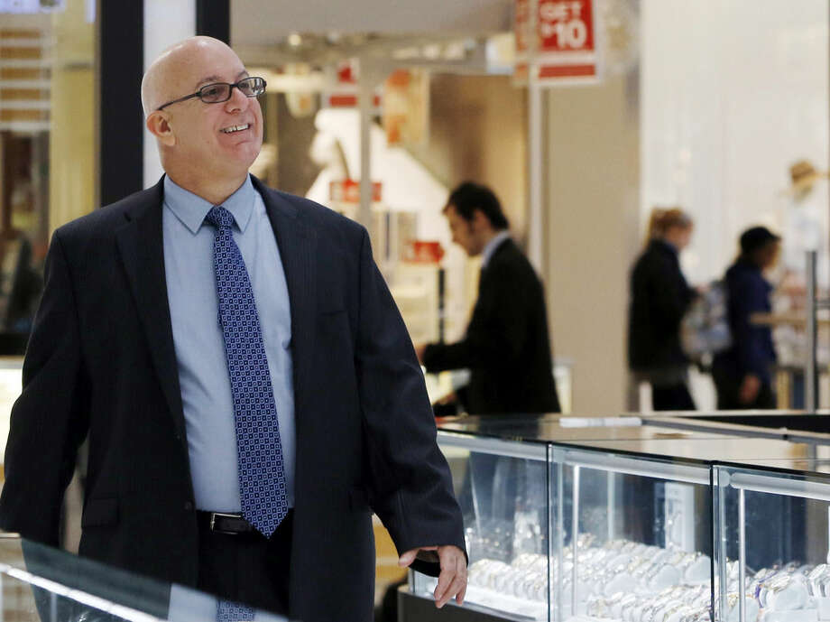 In this Wednesday, Nov. 18, 2015, photo, Jerry Amerosi walks to greet a customer at Gerald Peters jewelers, one of three stores he owns in the Staten Island Mall in New York. Amerosi's three stores will open at 6 p.m. on Thanksgiving and stay open until midnight. (AP Photo/Kathy Willens)