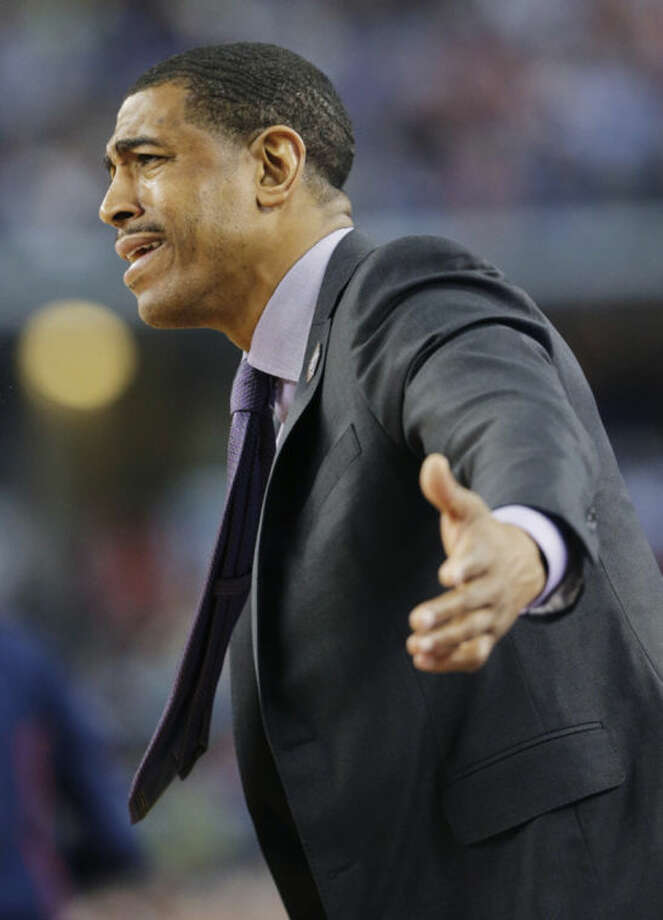 Connecticut head coach Kevin Ollie urges his team on during the first half of the NCAA Final Four tournament college basketball semifinal game against Florida Saturday, April 5, 2014, in Arlington, Texas. (AP Photo/Eric Gay)