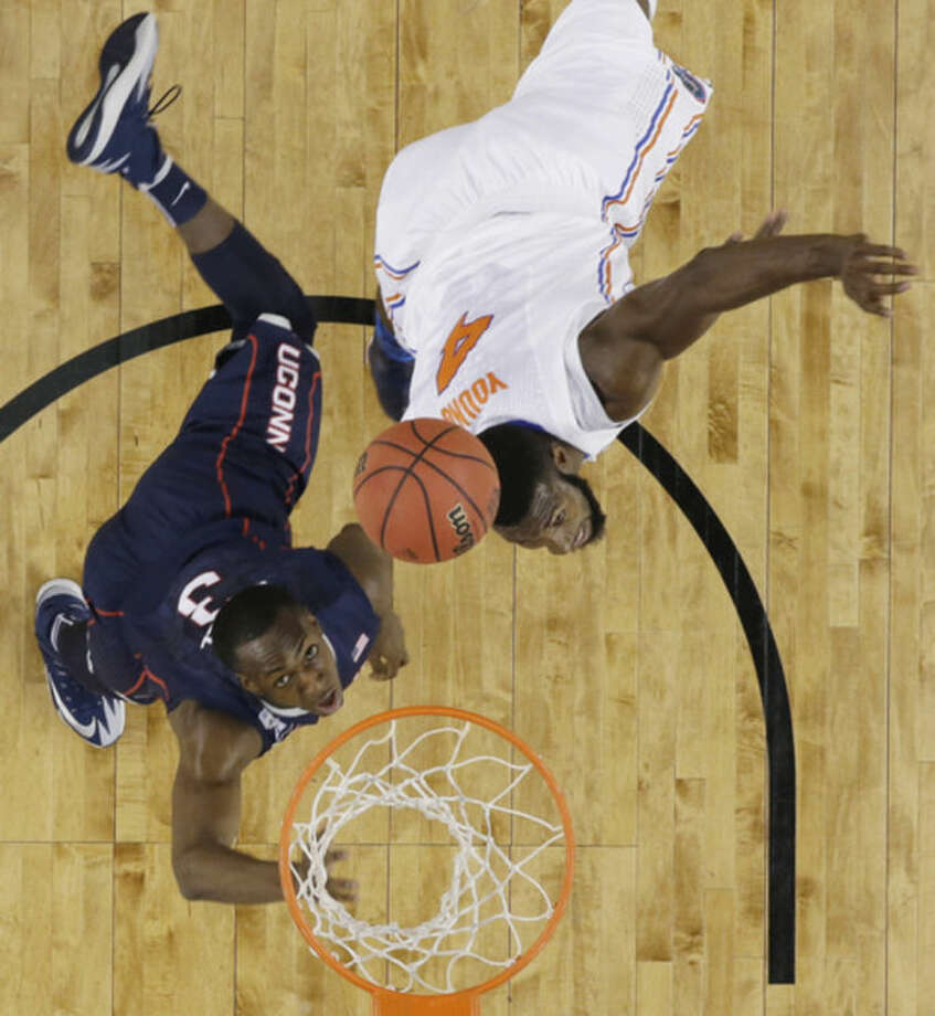 Connecticut guard Terrence Samuel, left, and Florida center Patric Young eye a rebound during the first half of an NCAA Final Four tournament college basketball semifinal game Saturday, April 5, 2014, in Arlington, Texas. (AP Photo/David J. Phillip)