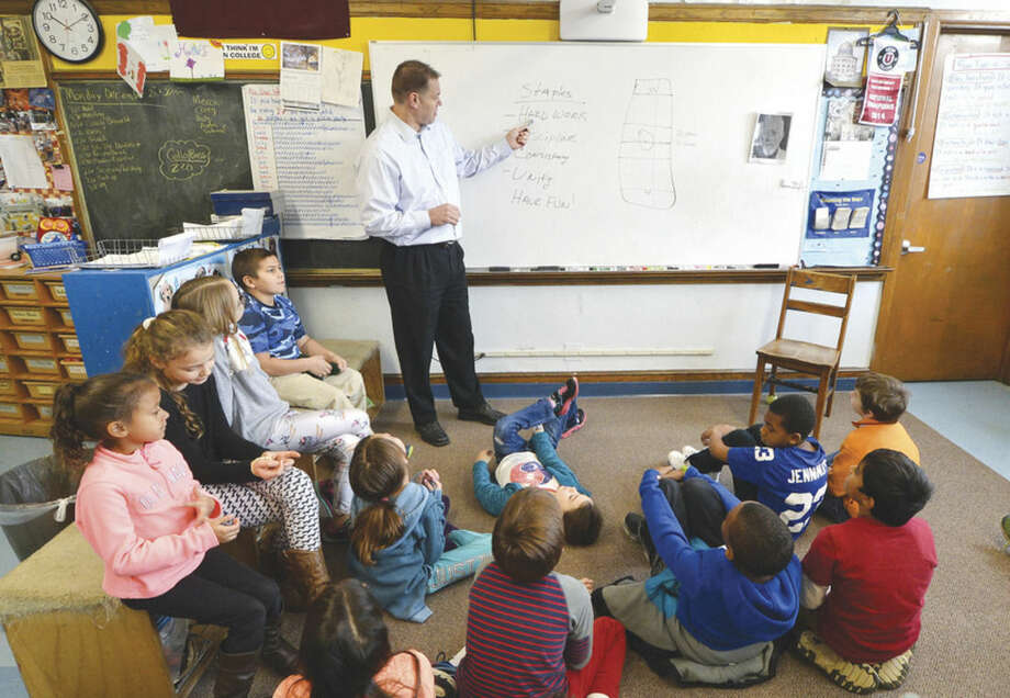 Hour Photo/Alex von Kleydorff Union College Hockey Coach Rick Bennett talks to Columbus Magnet School 4th graders in Andy Pearce's class about Think you can, work hard, Achieve