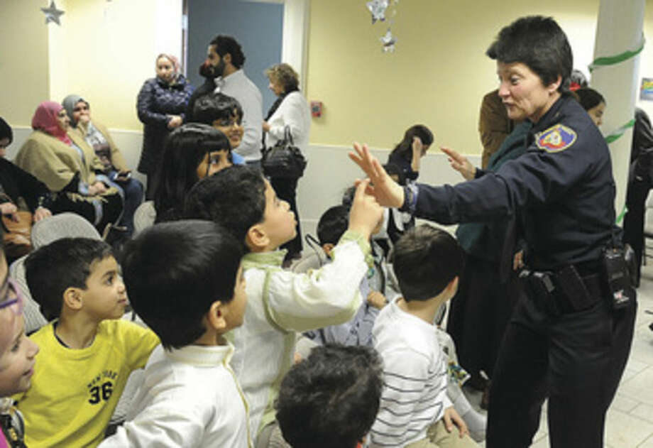 Hour photo/Matthew VinciStamford patrol Captain Susan Bretthauer hi-fives children at the ICCNY Islamic Cultural center Sunday where state officials, law enforcement and community leaders met to discuss the issue of backlash against the Muslim community.