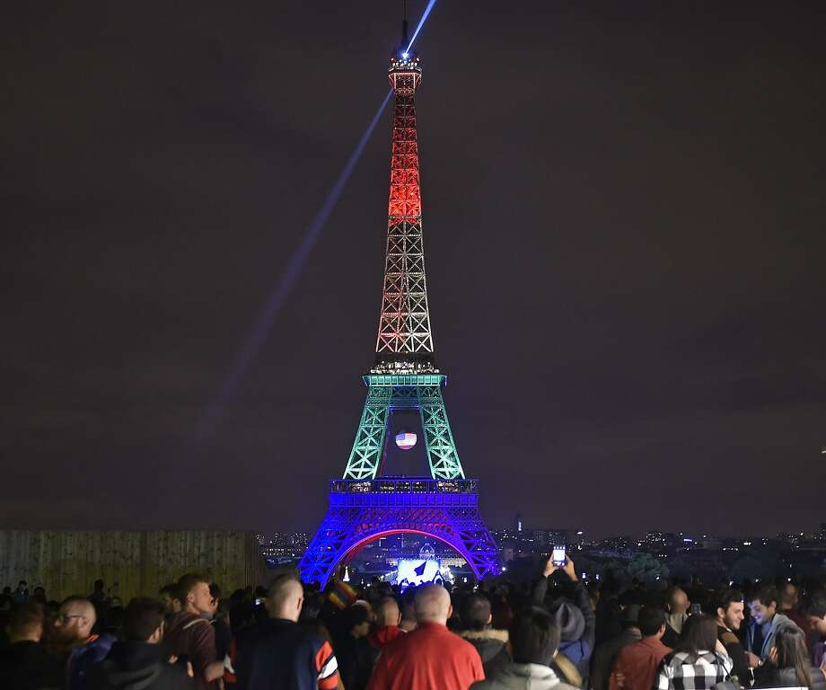 The Eiffel Tower in Paris, France, shines in the colors of a rainbow to honor victims of Sunday's mass shooting at an Orlando gay club, Monday, June 13, 2016. People brought banners, flags and candles to the Place Trocadero in front of the Paris landmark. Photo: Martin Meissner, Associated Press