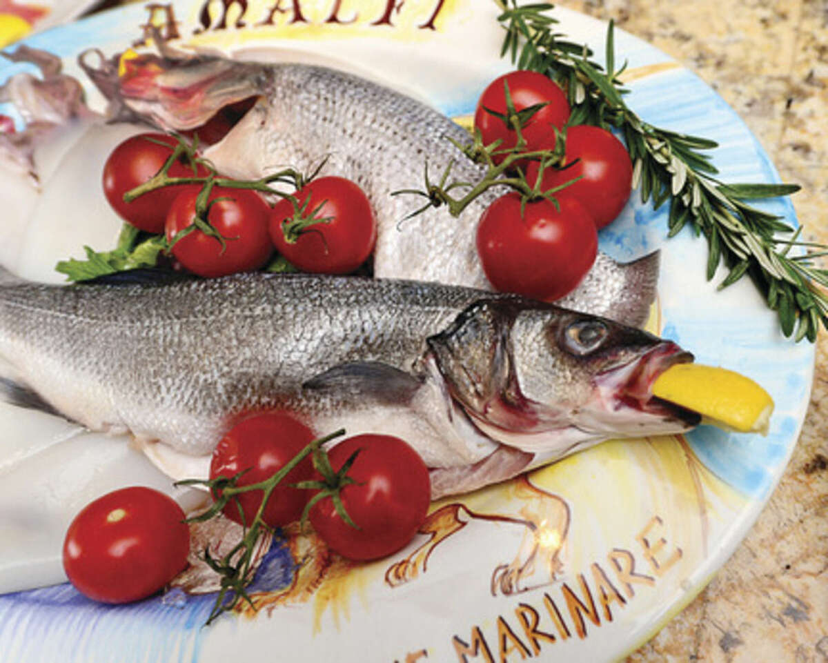 Hour photo / Erik Trautmann Giuseppe Cinque, owner of Quartina Trattoria, to serve the traditional Italian Seven Fishes Christmas Eve dishes including the Branzino and Bass at his restaurant on Washington St.