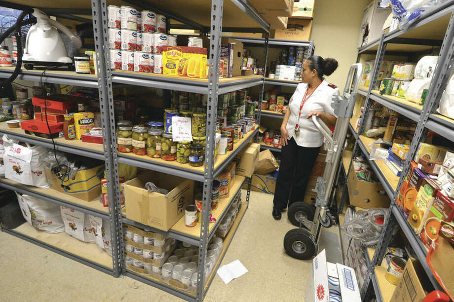 Hour photos/Alex von KleydorffAbove: Salvation Army Lt. Carmen Colon looks over the pantry that needs organizing after Thanksgiving at the Salvation Army offices in Norwalk. Middle below: Areminder for the bell ringers is posted to see as they leave the offices of the Salvation Army in Norwalk. Bottom: Colon gets a hug from client Angela Mera, who is picking up Christmas toys for her 3-year-old daughter.
