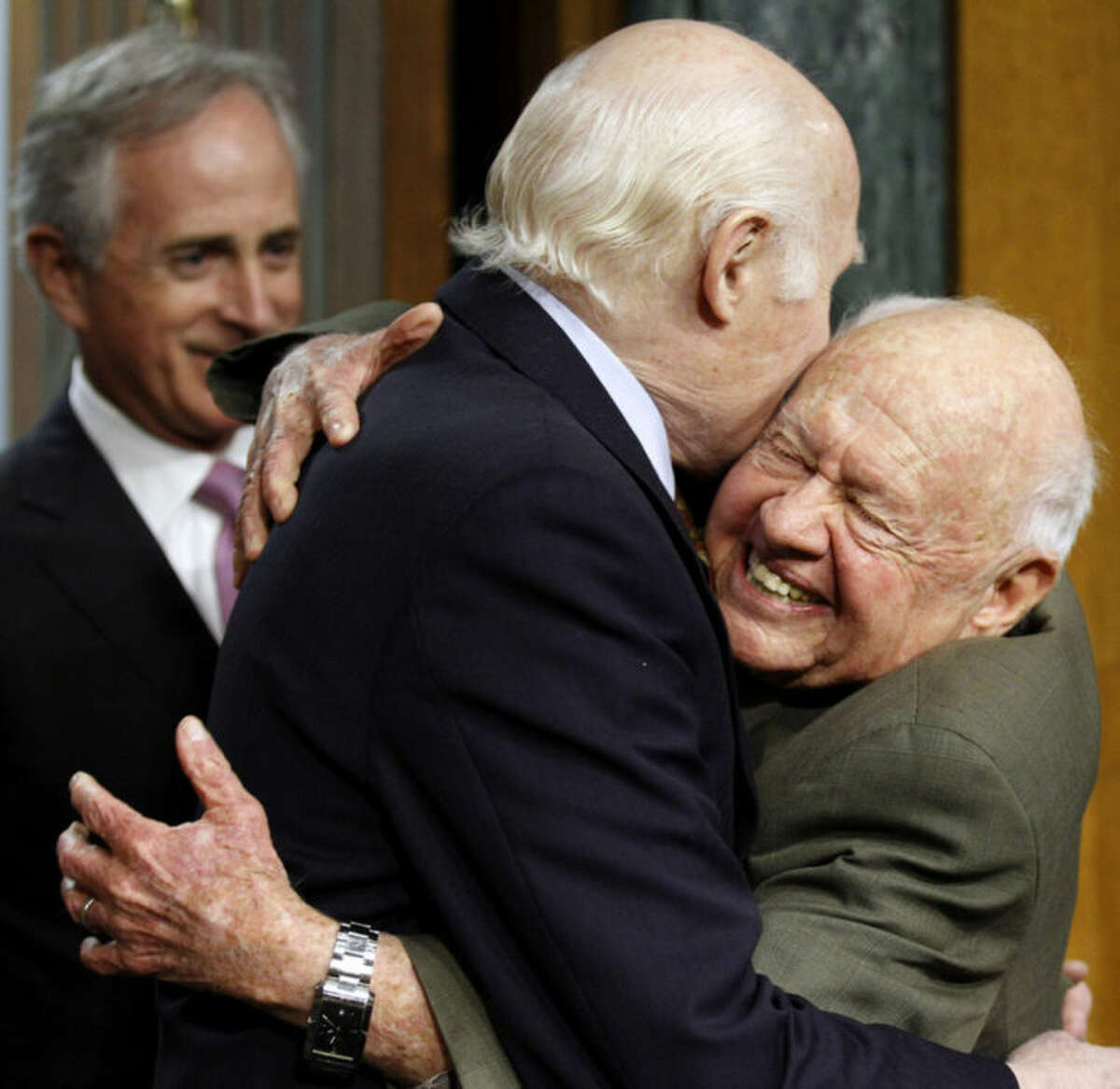 FILE - In this Wednesday, March 2, 2011, file photo, Senate Aging Committee Chairman Sen. Herb Kohl. D-Wis., center, gets a hug from entertainer Mickey Rooney, right, on Capitol Hill in Washington, as Sen. Bob Corker, R-Tenn., looks on at left, prior to Rooney testifying about elder abuse, before the committee. Rooney, a Hollywood legend whose career spanned more than 80 years, has died. He was 93. Los Angeles Police Commander Andrew Smith said that Rooney was with his family when he died Sunday, April 6, 2014, at his North Hollywood home. (AP Photo/Alex Brandon, File)
