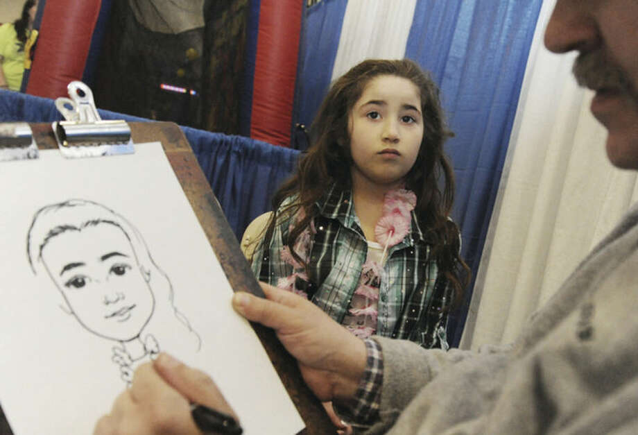 Leslie Rosara, 7, getting her picture drawn by caricatures by Mike Valentine Sunday at the Kids Fest held in the Wilton High School Field House.