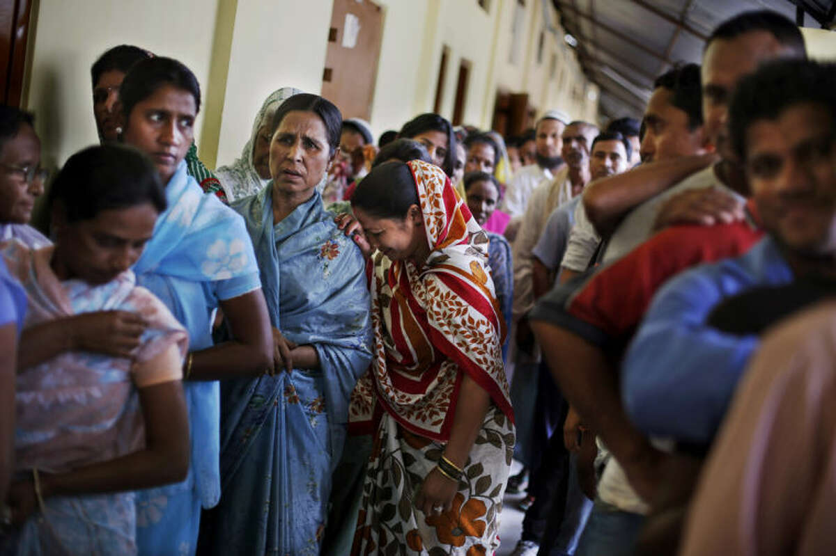 An Indian woman rests her head on the shoulder of another woman as they stand in a queue to cast their votes during the first phase of elections in Dibrugarh, in the northeastern state of Assam, India, Monday, April 7, 2014. India started the world's largest election Monday, with voters in the remote northeast making their way past lush rice paddies and over rickety bamboo bridges to reach the polls. The country's 814 million electorate will vote in stages over the next five weeks. (AP Photo/Altaf Qadri)
