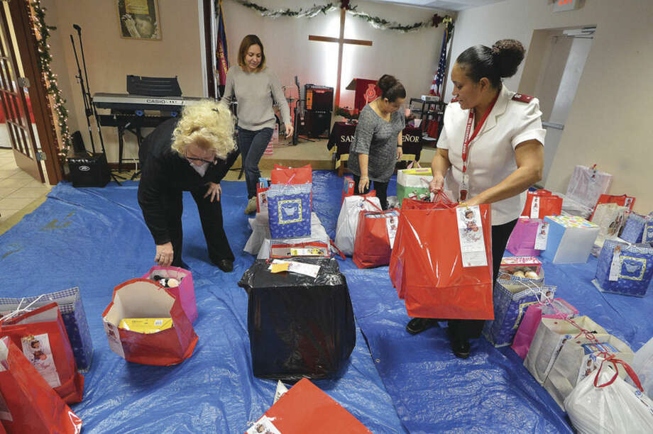 Hour photo/Alex von KleydorffFrom left: Charlotte Dufrane, Monica Cervantes, Carla Santos and Salvation Army Lt. Carmen Colon sort through bags of gifts and food donated for many families who are helped through the Salvation Army.