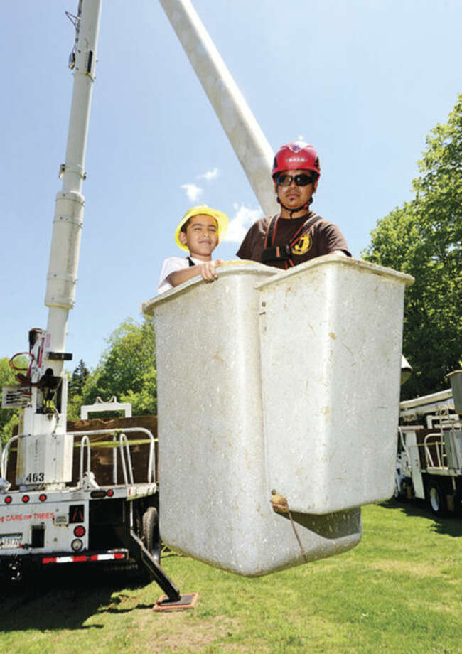 Hour photo / Erik Trautmann The Care of Trees Moris Duarte takes 6 year old Derek Porodomo up in a cherry picker during the 7th annusl Connecticut Tree Festival Saturday at Cranbury Park.