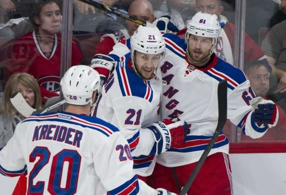 New York Rangers' Rick Nash (61) celebrates with teammates Chris Kreider (20) and Derek Stepan after scoring against the Montreal Canadiens during the first period in Game 2 of the NHL Eastern Conference final Stanley Cup playoff game in Montreal, Monday, May 19, 2014. (AP Photo/The Canadian Press, Graham Hughes)