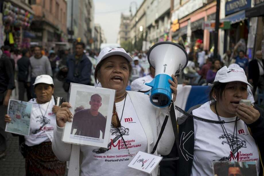 Central American women hold photographs of their disappeared family members as they march in Mexico City, Wednesday, Dec. 9, 2015. The caravan of women is traveling through Mexico to search for their missing relatives who left for a better life in the U.S. but disappeared. (AP Photo/Eduardo Verdugo)