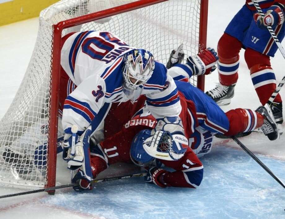New York Rangers goalie Henrik Lundqvist (30) is up ended by Montreal Canadiens right wing Brendan Gallagher (11) and Rangers left wing Rick Nash (61) during first period in game two of the NHL Eastern Conference final Stanley Cup playoff action Monday, May 19, 2014 in Montreal. (AP Photo/The Canadian Press, Ryan Remiorz)