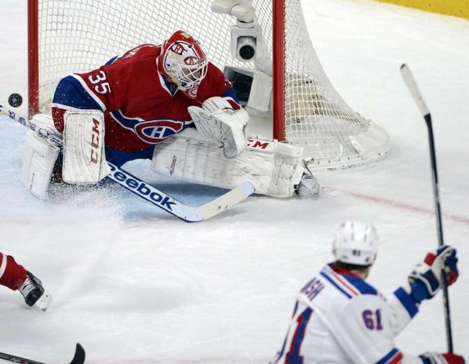 New York Rangers left wing Rick Nash (61) scores the second goal against Montreal Canadiens goalie Dustin Tokarski (35) during first period in game two of the NHL Eastern Conference final Stanley Cup playoff action Monday, May 19, 2014 in Montreal. (AP Photo/The Canadian Press, Ryan Remiorz)