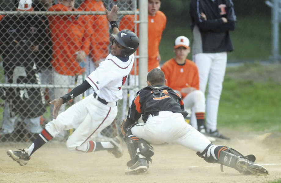 Hour photo/John NashBrien McMahon's Edwin Owolo, left, slides around the tag of Ridgefield catcher Joseph Coyle during Monday's FCIAC baseball game in Norwalk.