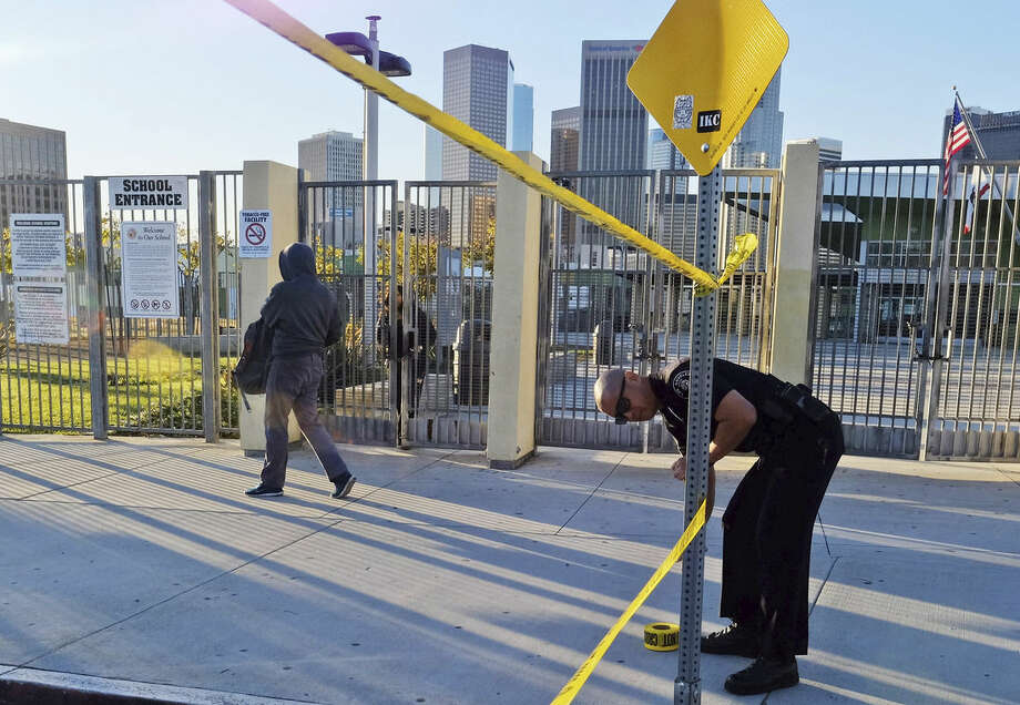 A police officer puts up yellow tape to close the school, as a student walks past, outside of Edward Roybal High School in Los Angeles, on Tuesday morning, Dec. 15, 2015. All schools in the vast Los Angeles Unified School District, the nation's second largest, have been ordered closed due to an electronic threat Tuesday. (AP Photo/Richard Vogel)