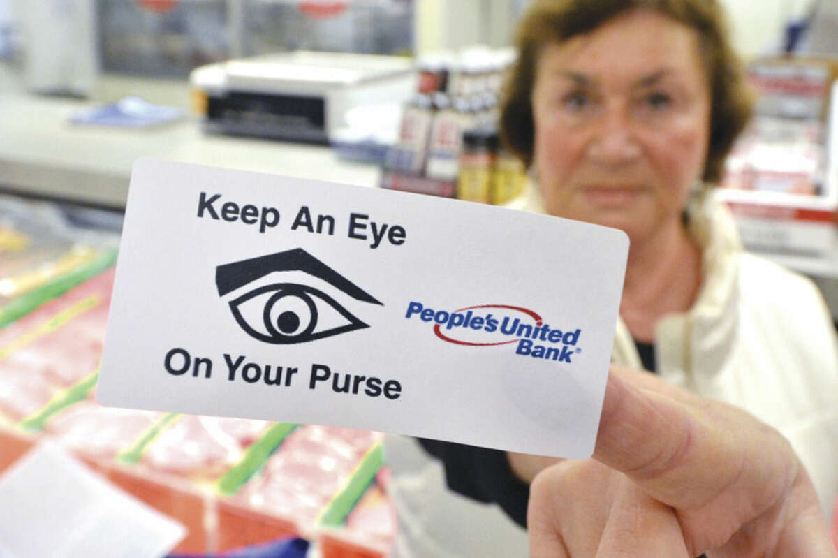 Hour Photo/Alex von Kleydorff If Angela DeLeon with Peoples United Bank puts this stiicker on your purse, you are not keeping an eye on it while shopping, during Purse Patrol