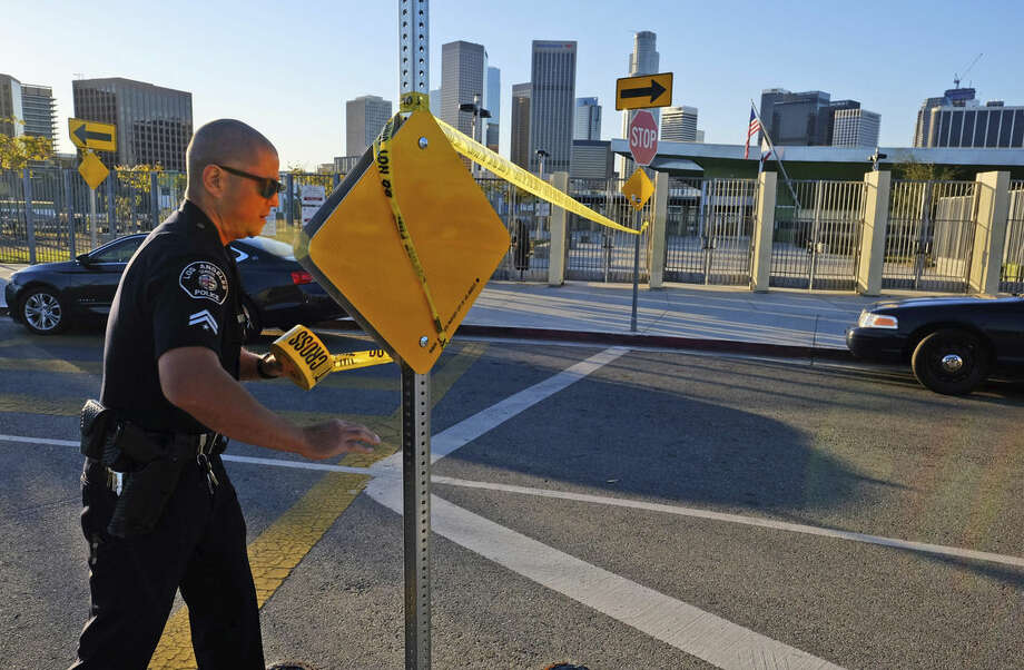 A police officer puts up yellow tape to close the school outside of Edward Roybal High School in Los Angeles, on Tuesday morning, Dec. 15, 2015. All schools in the vast Los Angeles Unified School District, the nation's second largest, have been ordered closed due to an electronic threat Tuesday. (AP Photo/Richard Vogel)