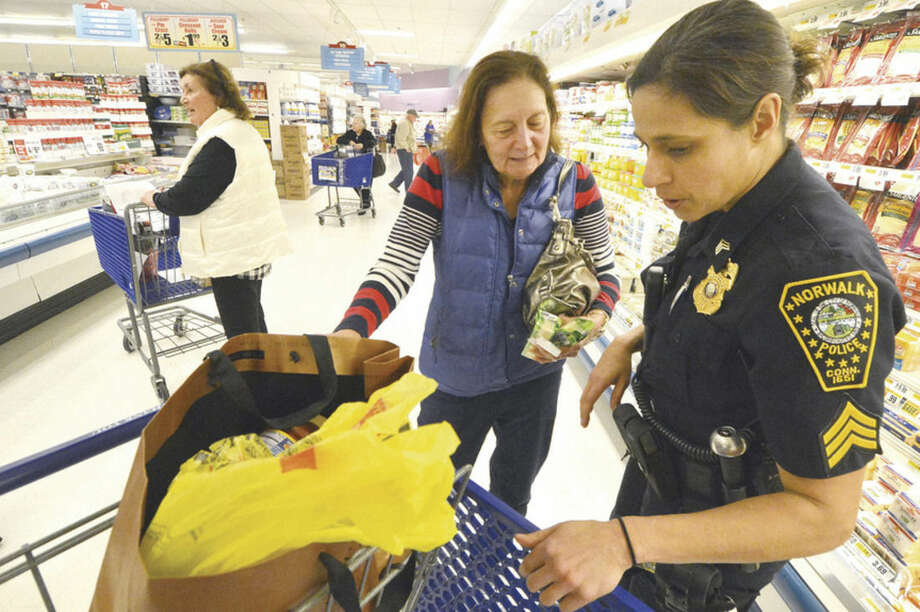 "Hour photo/Alex von KleydorffDuring a ""Purse Patrol,"" Angela DeLeon with Peoples United Bank moves on after placing a ""Keep an Eye On Your Purse"" sticker on Millie Florentine's purse. Norwalk Police Sgt. Sofia Gulino talks with her about the importance of keeping her purse secure, especially during the holidays."