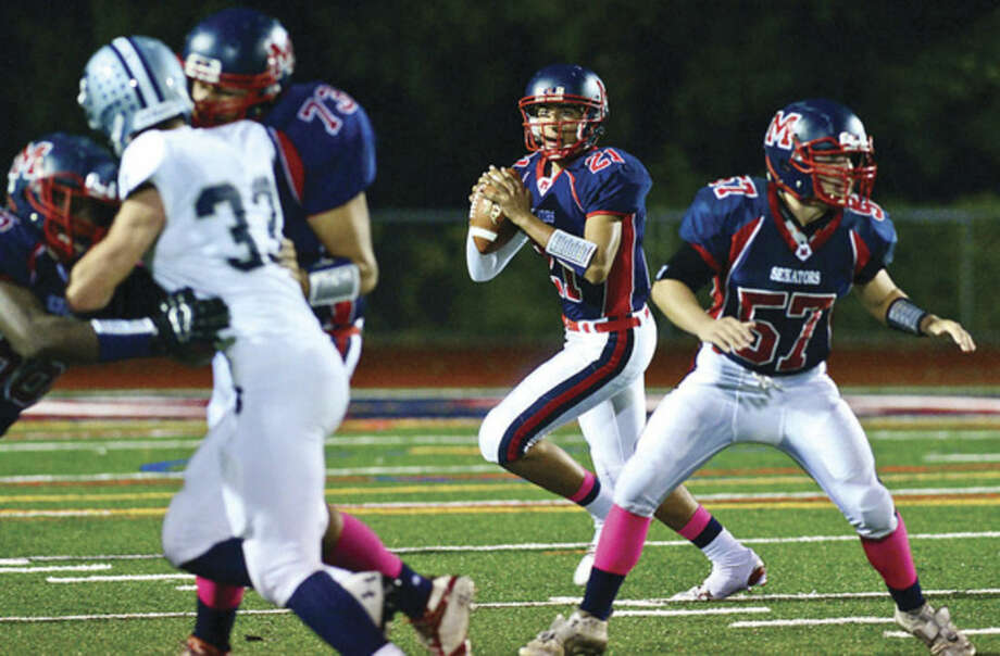 Hour photo/Erik TrautmannBrien McMahon quarterback Chris Druin (21) looks for an open receiver during Friday's FCIAC encounter against Staples at Casagrande Field in Norwalk.