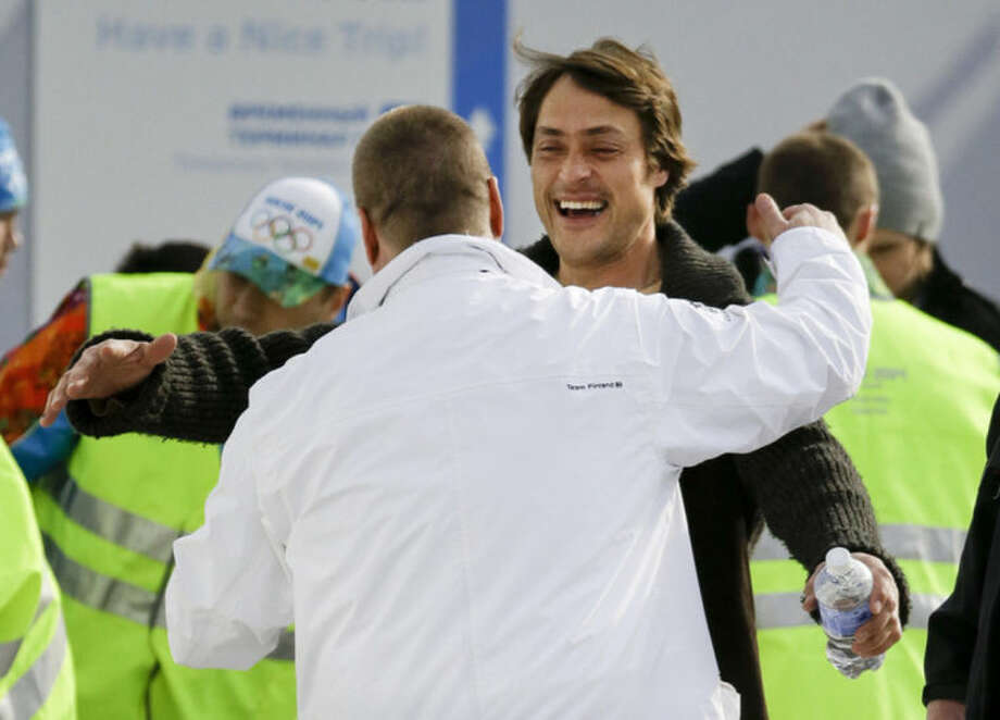 Anaheim Ducks forward Teemu Selanne, who will be playing for Finland, hugs a friend as he arrives with other NHL hockey players at the Sochi International Airport for the 2014 Winter Olympics, Monday, Feb. 10, 2014, in Sochi, Russia. (AP Photo/Mark Humphrey)