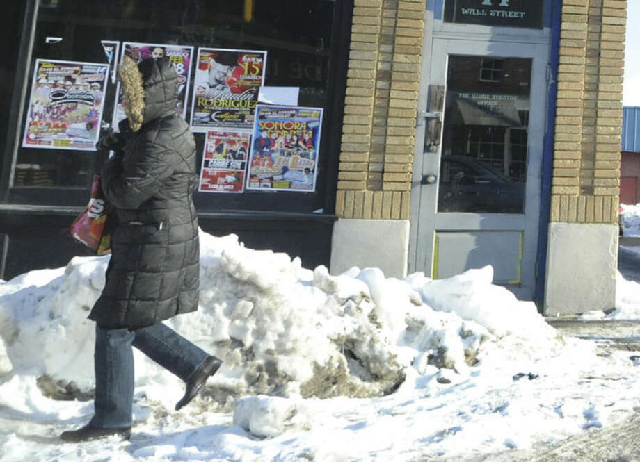 Some areas of piled snow in Norwalk like this spot on a corner of West Avenue makes for difficult passing for pedestrians. Hour photo/Matthew Vinci