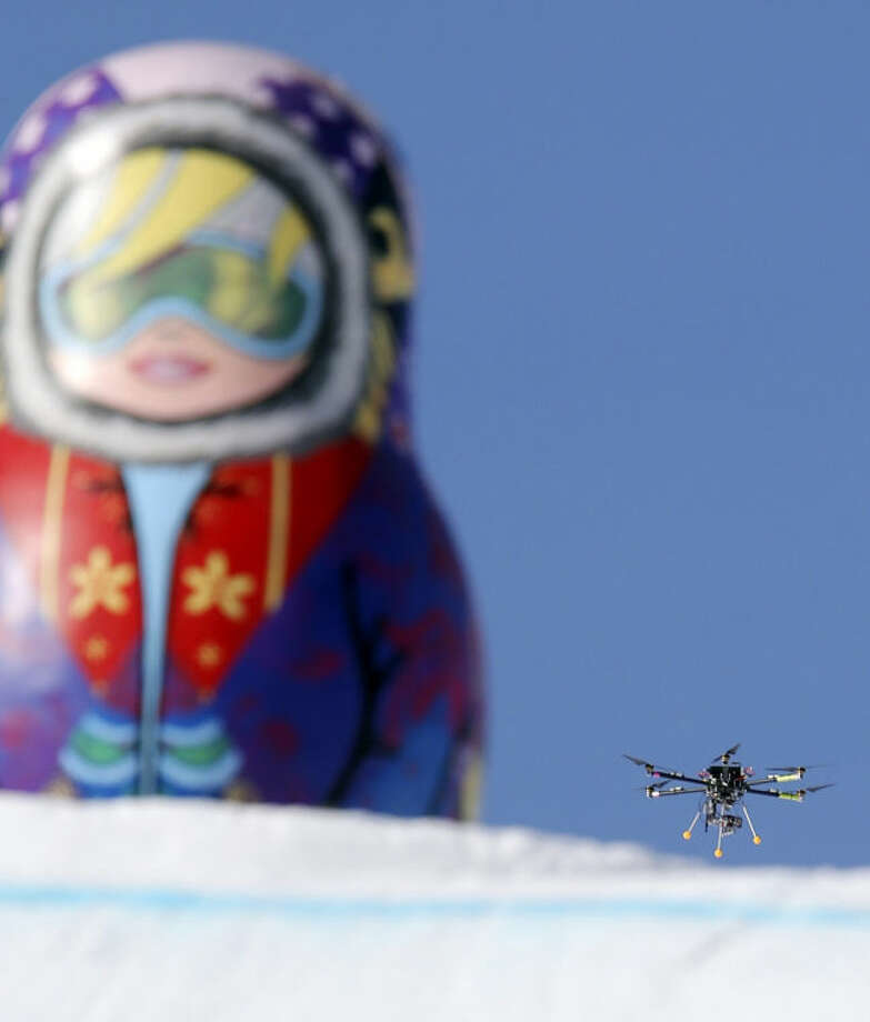 FILE -- In this Friday Feb. 7, 2014 file photo, a drone camera flies about the slopestyle course during a training session at the Rosa Khutor Extreme Park ahead of the 2014 Winter Olympics in Krasnaya Polyana, Russia. In the United States, the Federal Aviation Administration is developing new rules as the technology makes drones far more versatile, but for now operators can run afoul of regulations by using them for commercial purposes, including journalism. (AP Photo/Sergei Grits, File)