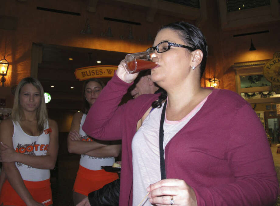 Nadina Fornia, of Egg Harbor Township, N.J., tastes a bloody Mary mixed with bacon-flavored beer at the Tropicana Casino and resort in Atlantic City, N.J. on Monday, Feb. 10. 2014. She said it tasted more like tomato juice than anything else. The casino's Bacon Week festival includes unusual offerings like bacon milk shakes, bacon cupcakes, bacon bloody Marys, beer, vodka and bourbon, and even bacon-flavored toothpaste, dental floss and lip balm. (AP Photo/Wayne Parry)