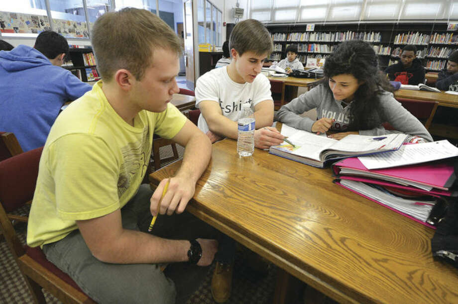 Hour Photo / Alex von Kleydorff.Norwalk High School Seniors Keith Purdie and Evan Czako help Nathan Hale 8th grader Jessica Alvarez with some history lessons during the Norwalk tutors B.A.R.K. program.