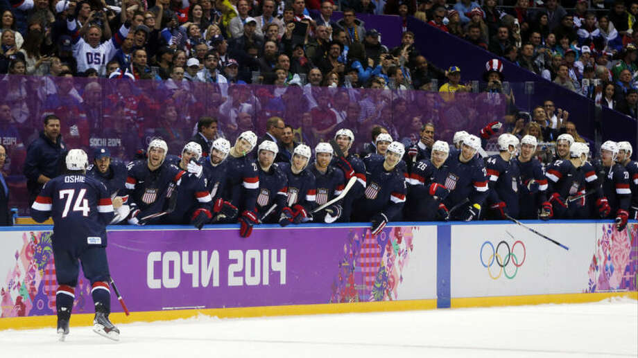 USA forward T.J. Oshie is greeted by teammates after scoring a goal against Russia during a shootout of a men's ice hockey game at the 2014 Winter Olympics, Saturday, Feb. 15, 2014, in Sochi, Russia. (AP Photo/Julio Cortez)