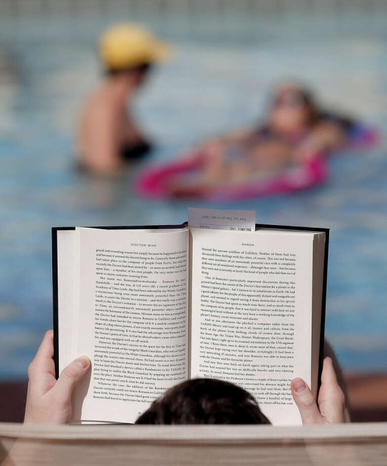 """Robert Wasik, of Minnesota, reads """"Dr. Who"""" poolside as guest float in the pool at the Mission Palms, Friday, Feb. 14, 2014 in Tempe, Ariz. With large parts of the country in the grips of frigid cold and snow and ice storms, the Southwest is enjoying a heat wave that is setting record highs and sending people to pools, golf courses and beaches in large numbers. Phoenix and Los Angeles are experiencing unusually warm 80-degree weather that has residents and visitors rejoicing as they look at the mess on the East Coast.(AP Photo/Matt York)"""