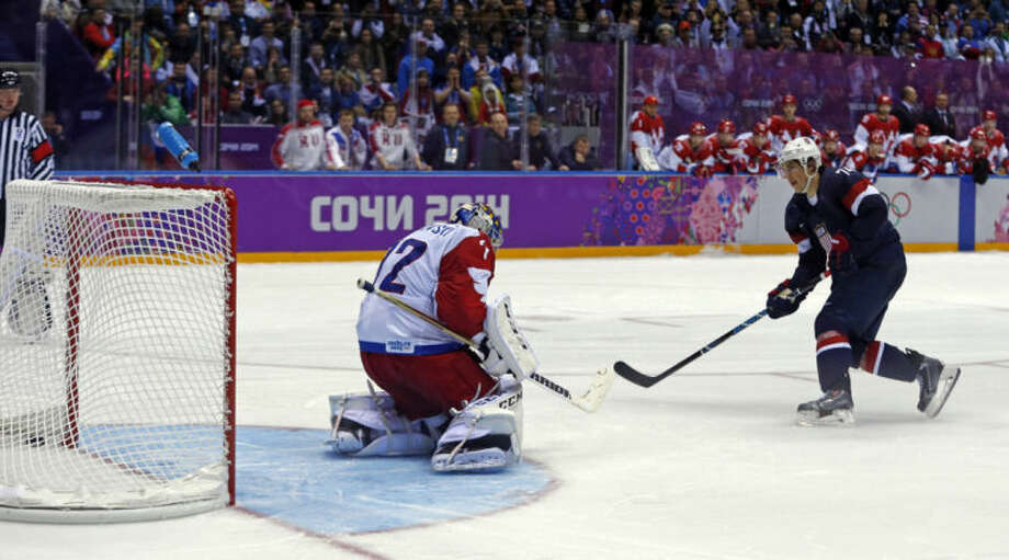 USA forward T.J. Oshie scores the winning goal against Russia goaltender Sergei Bobrovski in a shootout during overtime of a men's ice hockey game at the 2014 Winter Olympics, Saturday, Feb. 15, 2014, in Sochi, Russia. (AP Photo/Julio Cortez)