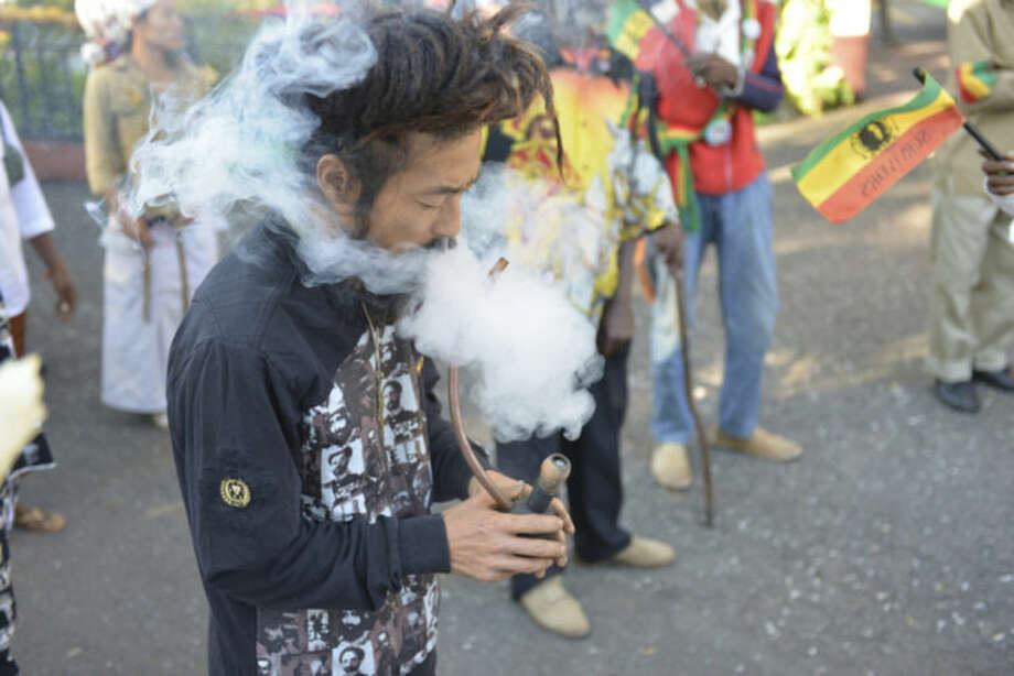 """ADVANCE FOR USE SUNDAY, FEB. 16, 2014, AND THEREAFTER - FILE - In this Feb. 6, 2013 photo, a Rastafarian named Bongho Jatusy smokes a pipe of marijuana outside a museum dedicated to the memory of late reggae icon Bob Marley in Kingston, Jamaica. While marijuana is still illegal in Jamaica, where it is known popularly as """"ganja,"""" increasingly vocal advocates say that Jamaica could give its struggling economy a boost by taking advantage of the fact the island is nearly as famous for its marijuana as it is for beaches, reggae music and world-beating sprinters. Anxiety over U.S. reprisals has always doused reform efforts in Jamaica, including a broadly supported 2001 attempt to approve private use of marijuana by adults. (AP Photo/David McFadden, File)"""
